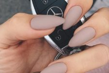 14 mauve-colored matte almond nails with an accent rhinestone nail