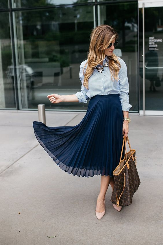 a chambray shirt, a navy pleated midi skirt, blush shoes, a statement necklace and a large bag