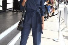 15 a navy jumpsuit with a sash, long sleeves, black retro shoes and a black bag for a formal look