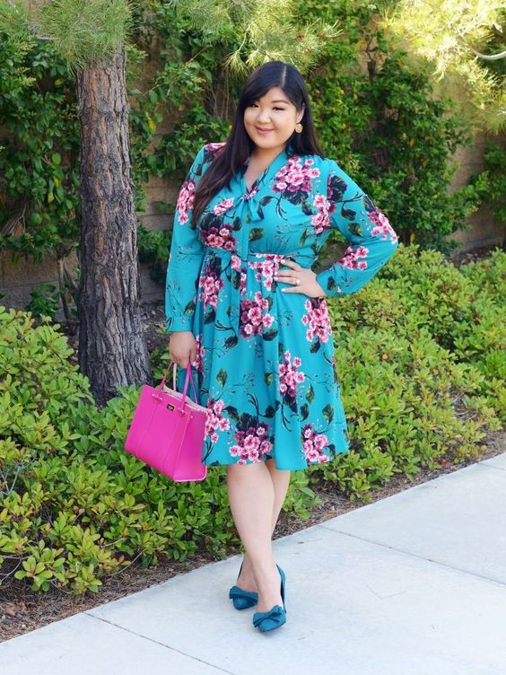 a turquoise plus size knee dress with long sleeves and a bow, turquoise bow flats and a pink bag