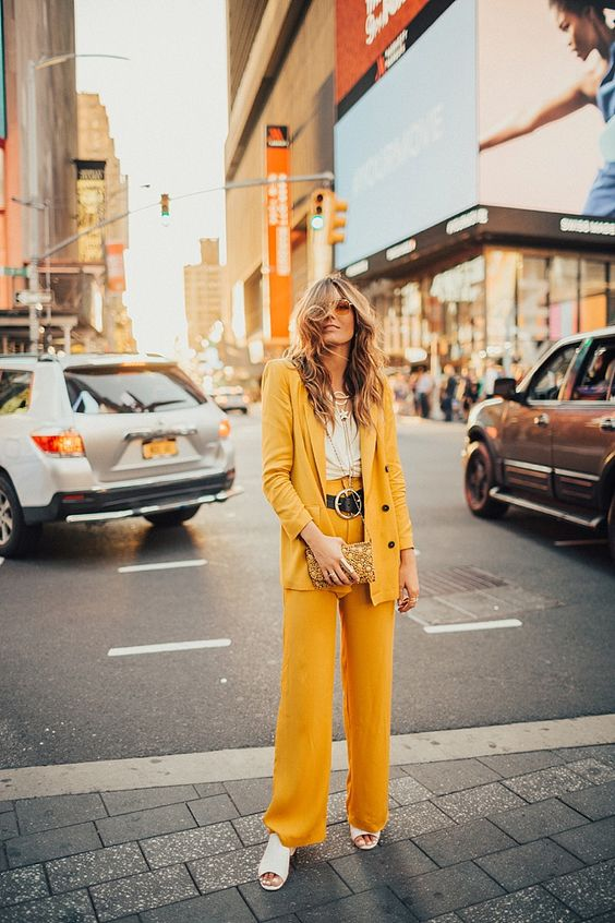 a yellow pantsuit, a white top, white mules and layered necklaces for a free spirited look