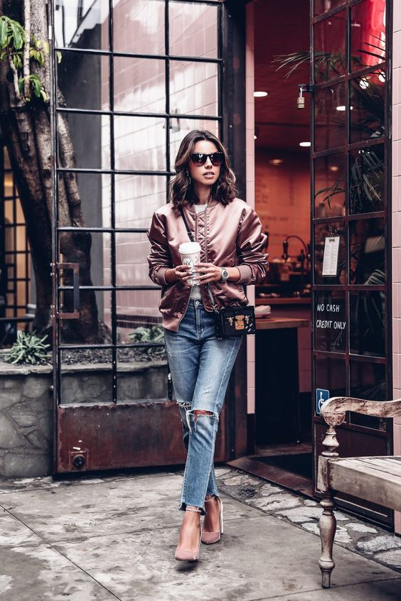 blush pumps, blue ripped raw edge jeans, a dusty pink bomber jacket and a small crossbody