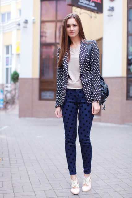 With beige shirt, navy blue polka dot pants, black bag and white shoes