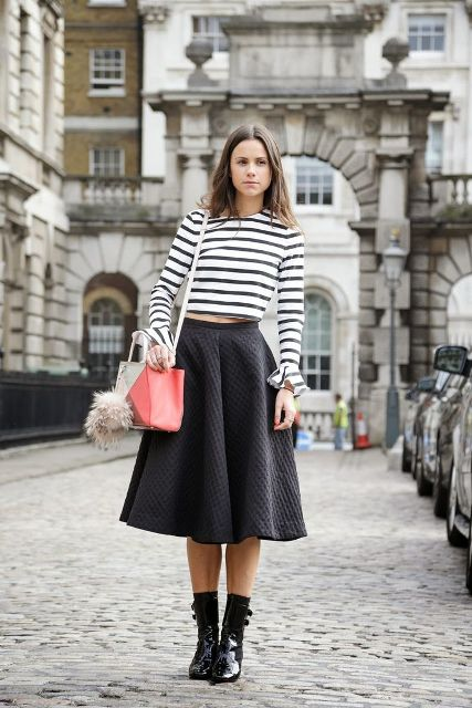 With black midi skirt, mid calf boots and beige and pink bag