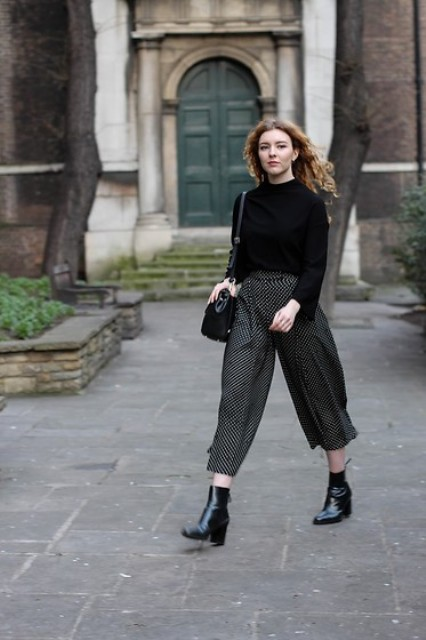 With black shirt, black ankle boots and bag