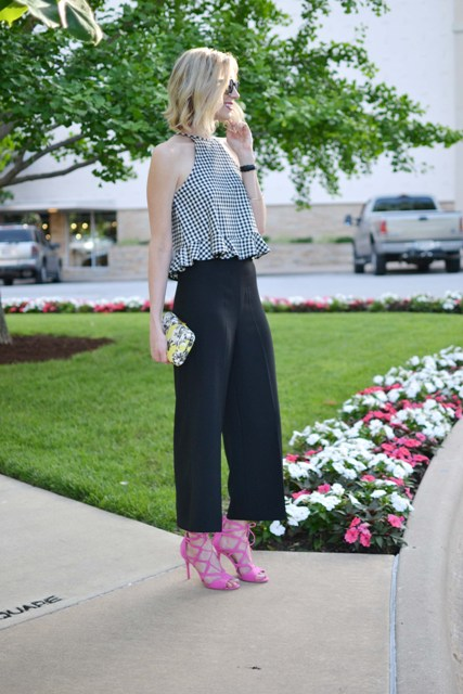 With black wide leg trousers, pink lace up sandals and printed clutch