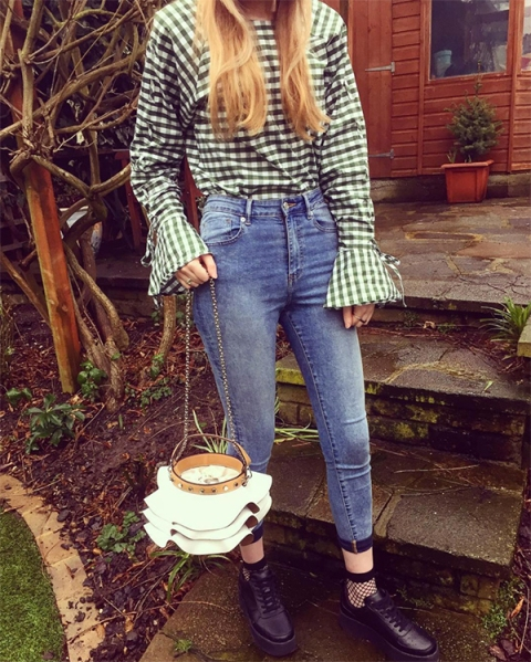 With checked blouse, skinny jeans, lace up shoes and unique bag