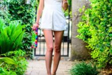 With colorful clutch and beige high heels