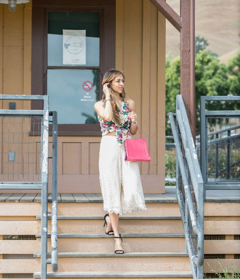 With floral top, black sandals and pink bag