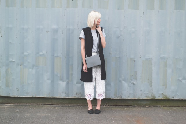 With gray t shirt, long vest, gray bag and flats