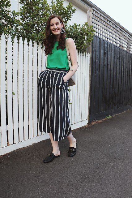 With green top, beige bag and black mules