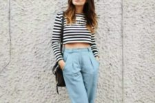 With light blue cuffed pants, black sandals and black bag