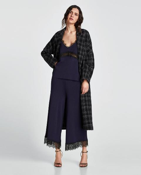 With navy blue top, checked coat and heels