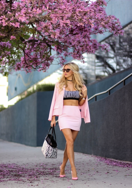 With pale pink blazer, pale pink skirt, pumps and printed bag