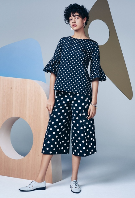 With polka dot blouse and flat shoes