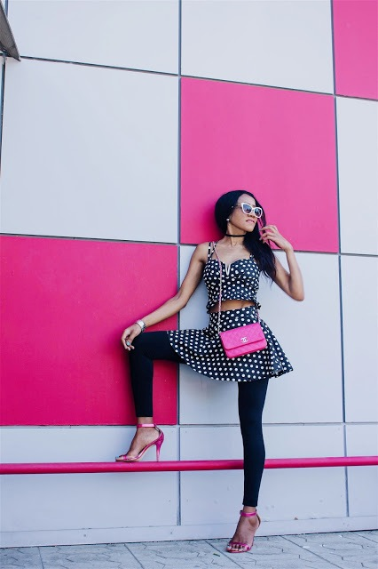 With polka dot skirt, black leggings, pink shoes and pink bag
