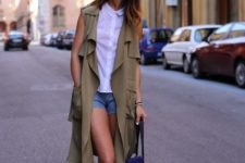 With shorts, lace up sandals, white button down shirt and bag