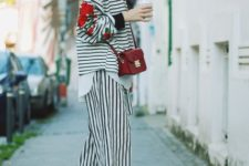 With striped loose shirt, black ankle boots and red mini bag