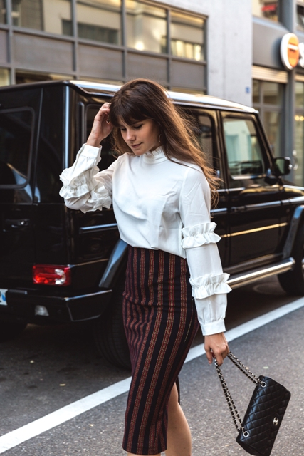 With striped skirt and black leather bag
