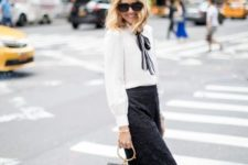 With white blouse, striped tie, white ankle boots and mini bag