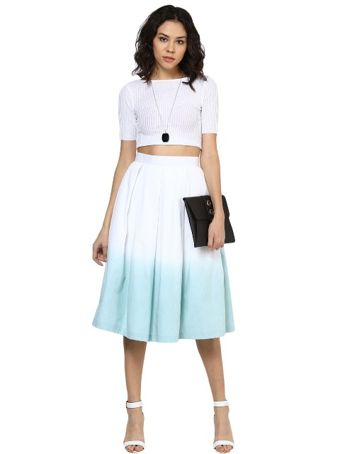 With white crop top, white sandals and black clutch