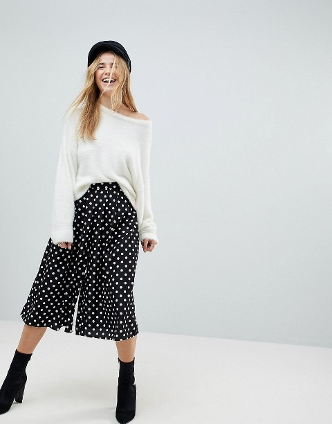 With white loose sweatshirt, black headband and mid calf boots