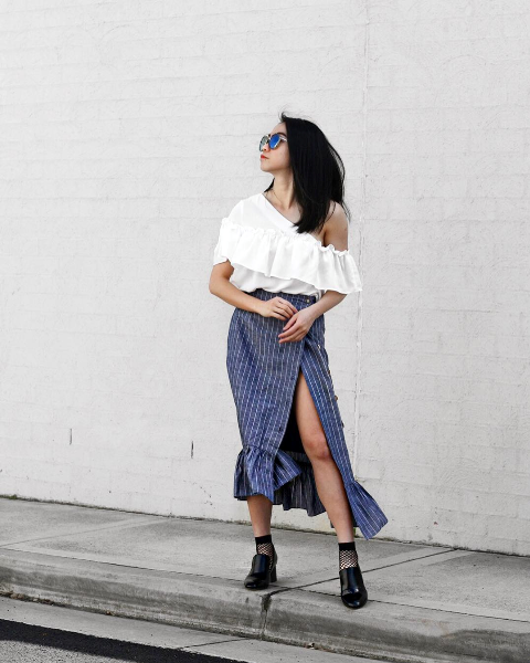 With white ruffle blouse, striped skirt and black shoes