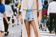 With white shirt, denim shorts, white shoes and brown bag