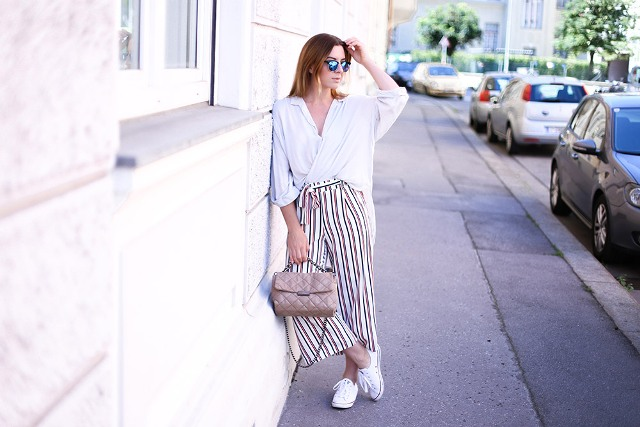 With white shirt, white sneakers and beige bag