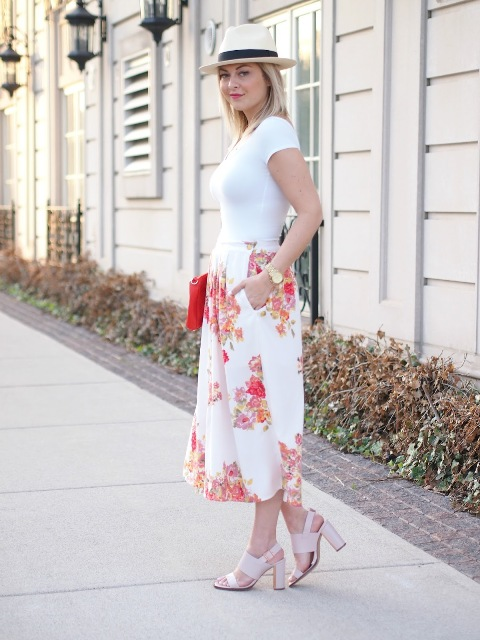 With white t-shirt, beige sandals, hat and red clutch