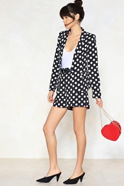 With white top, polka dot shorts, black shoes and red bag