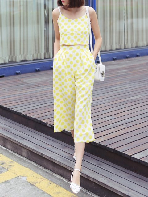 With yellow and white polka dot culottes, white shoes and white bag