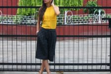With yellow blouse and beige sandals