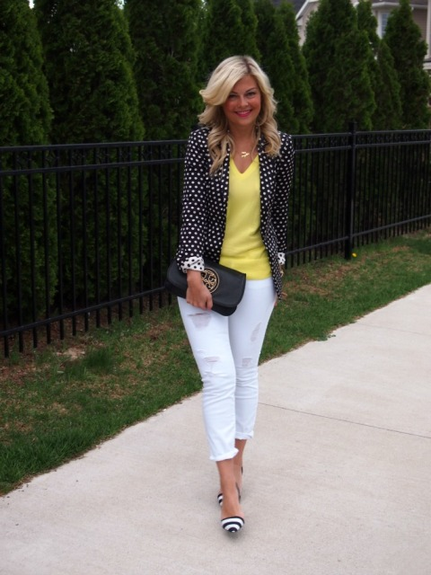 With yellow shirt, white cuffed pants, striped pumps and black clutch