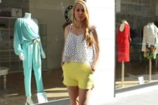 With yellow shorts and black sandals