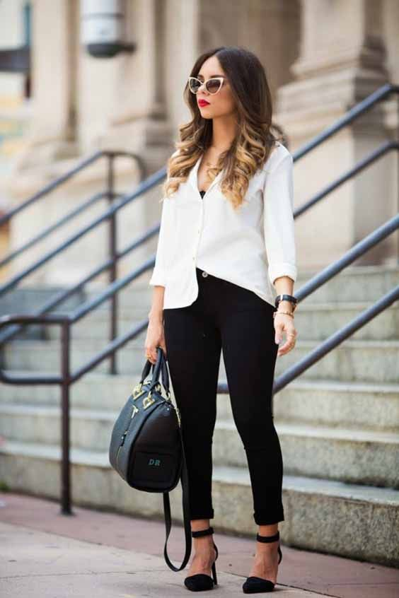 a black cropped pants, a white shirt over a black top, black ankle stra shoes and a black bag