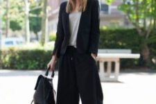 02 a black suit with culottes, a grey tee, black shoes and a black backpack for a chic modern look