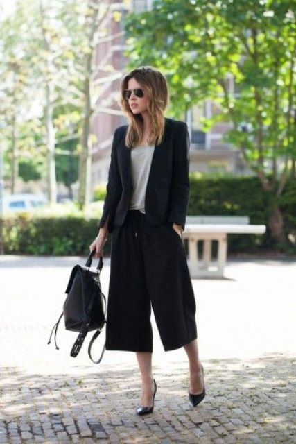 a black suit with culottes, a grey tee, black shoes and a black backpack for a chic modern look