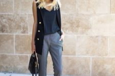 02 a black top and long vest with gold buttons and printed cropped pants, nude shoes and a black bag
