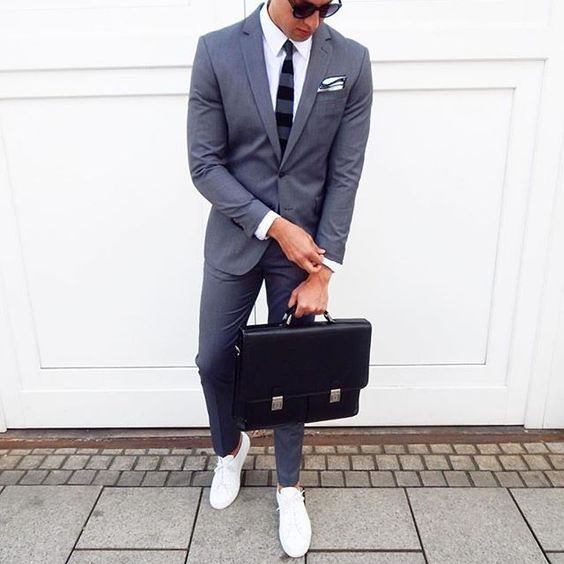 a grey suit, a white shirt, a striped tie and white sneakers for a modern feel
