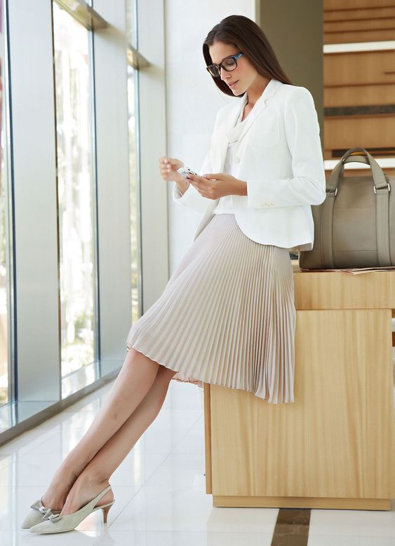 a white top, a white jacket, a blush pleated knee skirt, light grey kitten heels