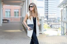 03 a black jumpsuit, a white long vest, floral lace up shoes and a black clutch for a bold look