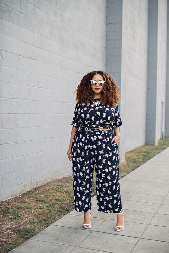 a navy floral print jumpsuit with short sleeves and white shoes is ideal for summer
