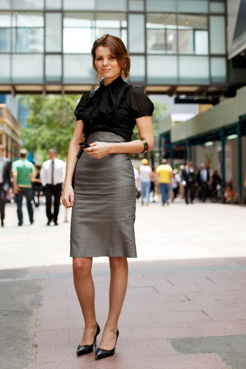 a high waisted grey over the knee skirt, a black bow blouse, black kitten heels for a tailored look