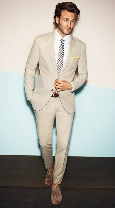 an off-white suit, a white shirt, a printed tie and light brown suede shoes