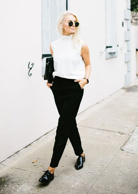 black pants, a sleeveless high neckline top, black lacquered leather shoes