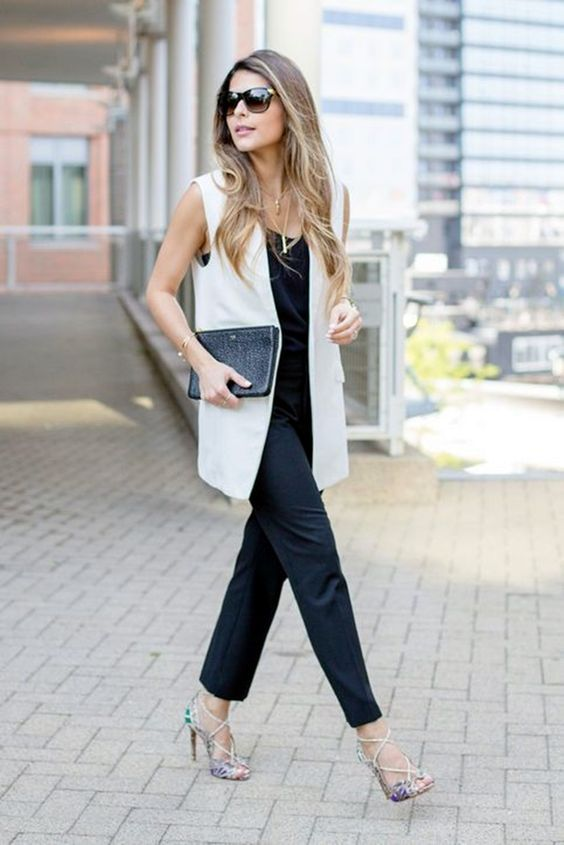 a black jumpsuit, a creamy long vest, a black clutch and floral strappy heels that spruce up the look