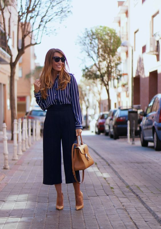 a vertical stripe blue and white shirt, navy culottes, a tan bag and shoes