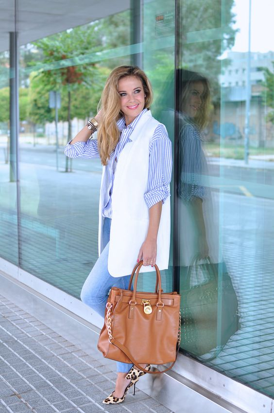 blue skinnies, a thin striped blue shirt, a white long vest, leopard print shoes and a tan bag