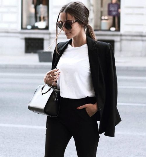 a black pantsuit, a white tee and a small black bag feel like minimalist chic